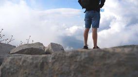 Caminante masculino irreconocible con la mochila que se coloca en el pico de la montaña y que disfruta de paisaje hermoso Cielo n almacen de metraje de vídeo