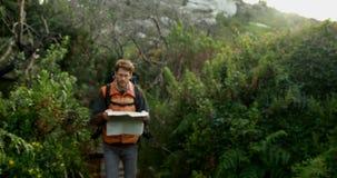 Caminante masculino que camina con el mapa en el campo 4k almacen de metraje de vídeo
