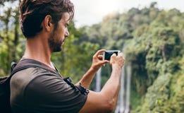 Caminante masculino que fotografía una caída del agua en bosque Imagenes de archivo