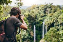 Caminante masculino que fotografía una cascada en bosque Foto de archivo
