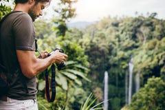 Caminante masculino que fotografía una cascada en bosque Imágenes de archivo libres de regalías