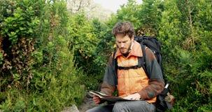 Caminante masculino que mira el mapa en el campo 4k almacen de video