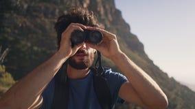 Caminante masculino que mira a través de los prismáticos mientras que se opone a la montaña almacen de video