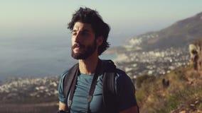 Caminante masculino sonriente que mira lejos mientras que dinking el agua contra el cielo metrajes