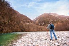 Caminante mayor en el banco de un río El caminar hacia la montaña Retiro activo Fotos de archivo