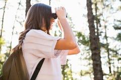 Caminante moreno sonriente que mira a través de los prismáticos Foto de archivo libre de regalías