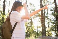 Caminante moreno sonriente que mira a través de los prismáticos Imagen de archivo
