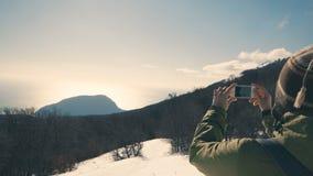 Caminante, muchacha que toma la imagen de la naturaleza salvaje con su smartphone, 4k del invierno almacen de video