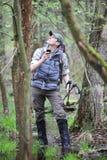 Caminante perdido en bosque con el dispositivo de la navegación del satélite móvil Imágenes de archivo libres de regalías