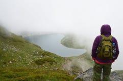 Caminante por un lago de la montaña en día nublado Foto de archivo libre de regalías
