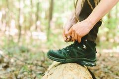 Caminante que ata cordones de la bota en un registro Imagen de archivo