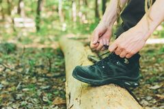 Caminante que ata cordones de la bota en un registro Fotografía de archivo libre de regalías