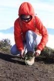 Caminante que ata el cordón en pico de montaña Imagenes de archivo