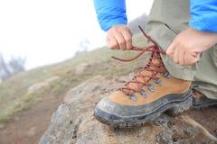 Caminante que ata el cordón en pico de montaña Imagen de archivo