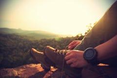 Caminante que ata el cordón en roca del pico de montaña Imágenes de archivo libres de regalías