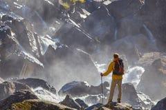Caminante que camina con la mochila que mira la cascada Fotografía de archivo