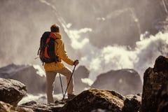 Caminante que camina con la mochila que mira la cascada Fotografía de archivo libre de regalías