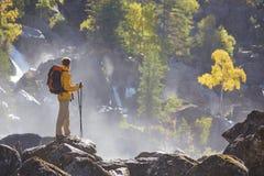 Caminante que camina con la mochila que mira el río de la montaña Fotos de archivo