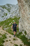 Caminante que camina en las montañas rocosas Imagen de archivo