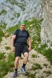 Caminante que camina en las montañas rocosas Imagen de archivo libre de regalías
