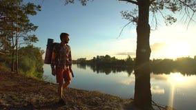 Caminante que camina a lo largo de la orilla del río en el lugar magnífico, disfrutando de hermosa vista almacen de metraje de vídeo
