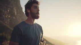 Caminante que come el plátano y la música que escucha en la montaña contra el cielo almacen de video