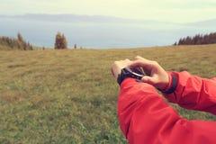 Caminante que comprueba el altímetro en el reloj de los deportes foto de archivo libre de regalías