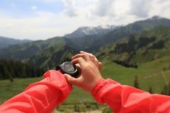 caminante que comprueba el altímetro en el reloj de los deportes en el pico de montaña imagen de archivo