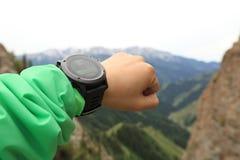 caminante que comprueba el altímetro en el reloj de los deportes en el pico de montaña imagenes de archivo