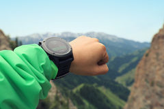 caminante que comprueba el altímetro en el reloj de los deportes en el pico de montaña imágenes de archivo libres de regalías