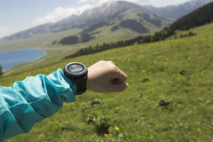 caminante que comprueba el altímetro en el reloj de los deportes en el pico de montaña fotografía de archivo