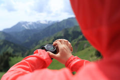 caminante que comprueba el altímetro en el reloj de los deportes en el pico de montaña foto de archivo
