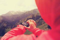 caminante que comprueba el altímetro en el reloj de los deportes en el pico de montaña foto de archivo libre de regalías