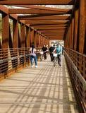 Caminante que cruzan un puente del metal en el Greenway del río de Roanoke fotografía de archivo libre de regalías