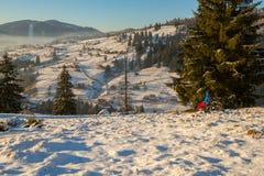 Caminante que descansa al borde de un pequeño pueblo en las montañas Fotografía de archivo