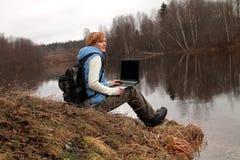 Caminante que descansa con el ordenador portátil Imagenes de archivo