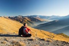 Caminante que descansa sobre el top de la montaña Imagen de archivo