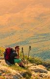 Caminante que descansa sobre rocas en montañas Imágenes de archivo libres de regalías