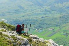 Caminante que descansa sobre rocas en montañas Imagen de archivo