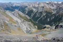 Caminante que descienden al valle alpino en las montañas meridionales Imágenes de archivo libres de regalías