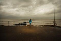 Caminante que hace una pausa el mar en un día tempestuoso Imagenes de archivo