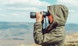 Caminante que mira en prismáticos en las montañas imagenes de archivo