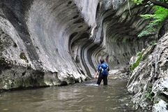 Caminante que pasa a través del agua en una garganta Imagen de archivo