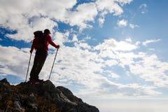 Caminante que se coloca en el top de una montaña Fotos de archivo libres de regalías