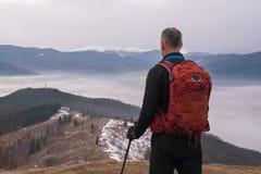 Caminante que se coloca en las montañas, mirando la niebla que flota abajo Imágenes de archivo libres de regalías