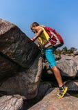 Caminante que sube en una roca Imagenes de archivo