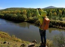 Caminante que toma la foto con smartphone en la montaña de la orilla Imagen de archivo libre de regalías