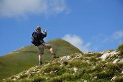 Caminante que toma las fotos en la montaña Foto de archivo