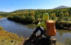 Caminante que usa smartphone en la montaña de la orilla Foto de archivo