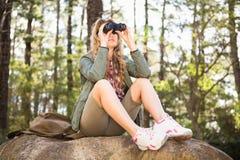 Caminante rubio que mira a través de los prismáticos y que se sienta en piedra Foto de archivo libre de regalías